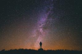 silhouette of person against multi-colored and starry night sky